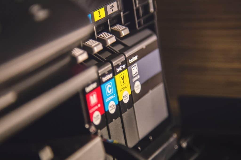 Musta, magenta, keltainen ja syaani mustekasetti tulostimessa.
